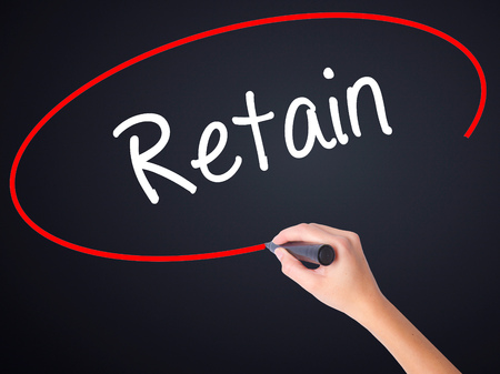 retained: Woman Hand Writing Retain on blank transparent board with a marker isolated over black background. Stock Photo