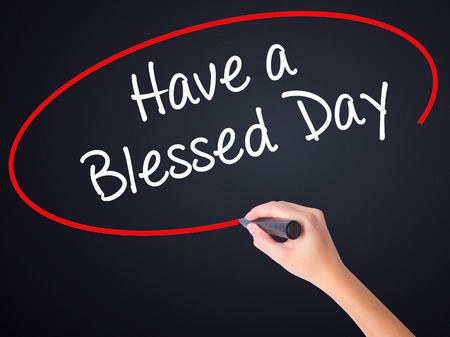 think through: Woman Hand Writing Have a Blessed Day  on blank transparent board with a marker isolated over black background. Stock Photo