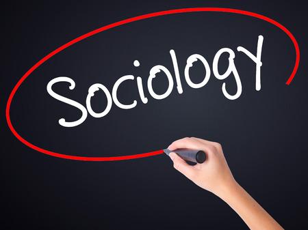 sociologia: Mujer escritura de la mano a bordo de Sociología transparente blanco con un marcador aislado sobre fondo negro. Foto de stock
