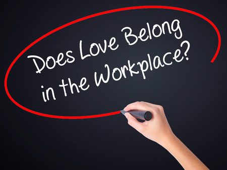 belong: Woman Hand Writing Does Love Belong in the Workplace? on blank transparent board with a marker isolated over black background. Business concept. Stock Photo