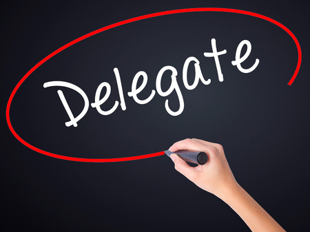 delegar: Woman Hand Writing Delegate on blank transparent board with a marker isolated over black background. Business concept. Stock Photo