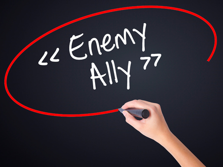 interdependence: Woman Hand Writing Enemy - Ally on blank transparent board with a marker isolated over black background. Stock Photo Stock Photo