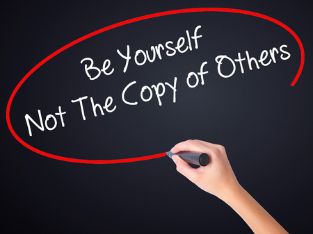 others: Woman Hand Writing Be Yourself Not The Copy of Others on blank transparent board with a marker isolated over black background. Business concept. Stock Photo