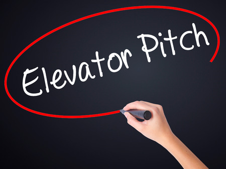 business pitch: Woman Hand Writing Elevator Pitch on blank transparent board with a marker isolated over black background. Business concept. Stock Photo