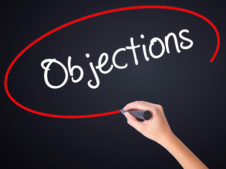 objections: Woman Hand Writing Objections  on blank transparent board with a marker isolated over black background. Business concept. Stock Photo