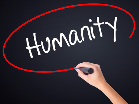 mercifulness: Woman Hand Writing Humanity  on blank transparent board with a marker isolated over black background. Stock Photo Stock Photo