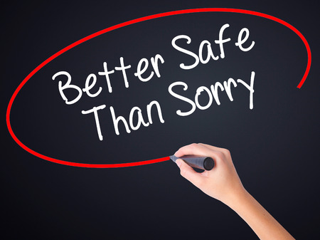 better safe than sorry: Woman Hand Writing Better Safe Than Sorry on blank transparent board with a marker isolated over black background. Stock Photo