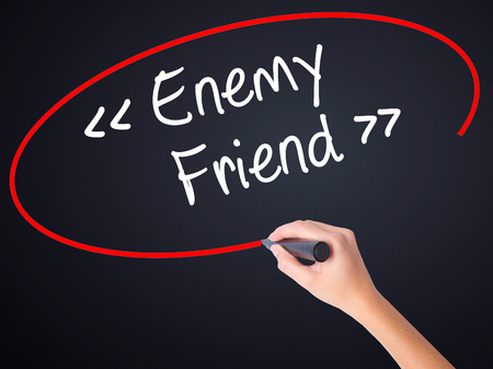 duplicitous: Woman Hand Writing Enemy - Friend on blank transparent board with a marker isolated over black background. Stock Photo