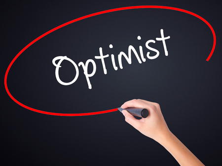 and an optimist: Woman Hand Writing Optimist  on blank transparent board with a marker isolated over black background. Business concept. Stock Photo Stock Photo