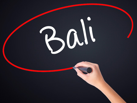 bali province: Woman Hand Writing Bali  on blank transparent board with a marker isolated over black background. Business concept. Stock Photo