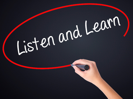 comprehend: Woman Hand Writing Listen and Learn on blank transparent board with a marker isolated over black background. Business concept. Stock Photo Stock Photo
