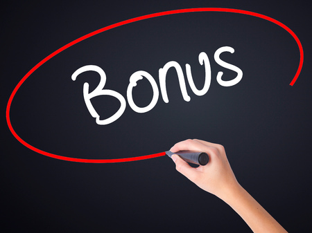 additional compensation: Woman Hand Writing Bonus on blank transparent board with a marker isolated over black background. Stock Photo