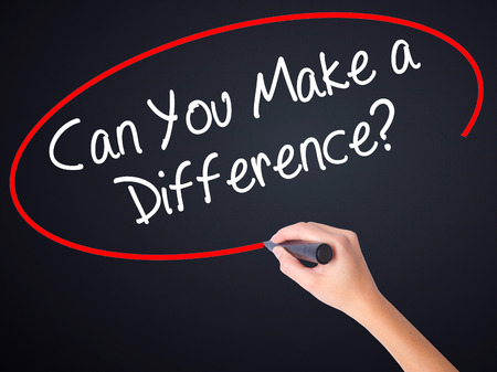 standout: Woman Hand Writing Can You Make a Difference? on blank transparent board with a marker isolated over black background. Stock Photo