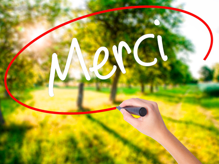 Woman Hand Writing Merci  (Thank You In French) on blank transparent board with a marker isolated over green field background. Stock Photo
