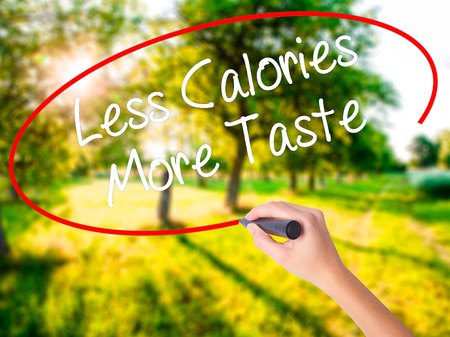 Woman Hand Writing Less Calories More Taste on blank transparent board with a marker isolated over green field background. Stock Photo