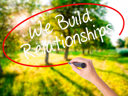 Woman Hand Writing We Build Relationships on blank transparent board with a marker isolated over green field background. Business concept. Stock Photo Stock Photo