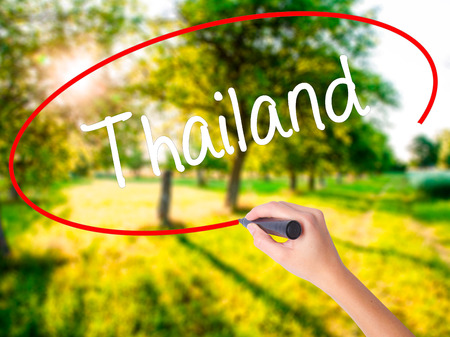Woman Hand Writing Thailand  on blank transparent board with a marker isolated over green field background. Business concept. Stock Photo