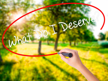 opinions: Woman Hand Writing What Do I Deserve? on blank transparent board with a marker isolated over green field background. Stock Photo
