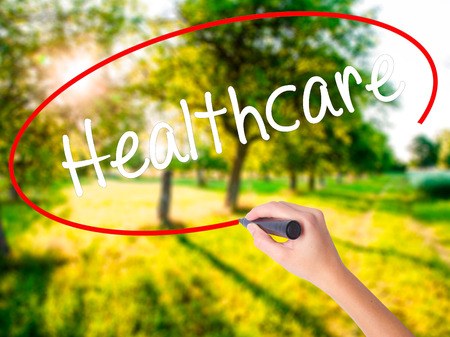 Woman Hand Writing Healthcare on blank transparent board with a marker isolated over green field background. Business concept. Stock Photo