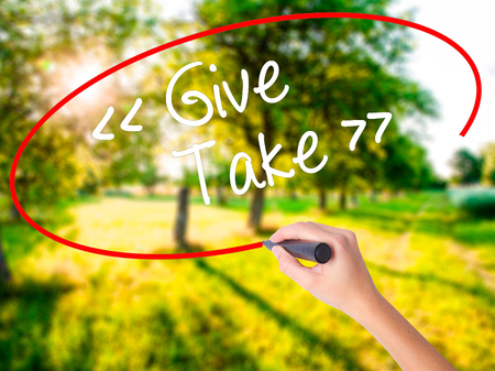 selfless: Woman Hand Writing Give - Take on blank transparent board with a marker isolated over green field background. Stock Photo