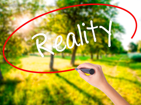 actuality: Woman Hand Writing  Reality on blank transparent board with a marker isolated over green field background. Business concept. Stock Photo