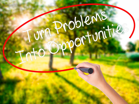 Woman Hand Writing Turn Problems into Opportunities on blank transparent board with a marker isolated over green field background. Stock Photo