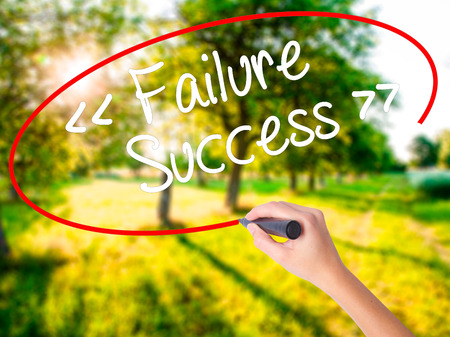 Woman Hand Writing Failure Success on blank transparent board with a marker isolated over green field background. Stock Photo Stock Photo