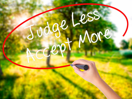 Woman Hand Writing Judge Less Accept More on blank transparent board with a marker isolated over green field background. Stock Photo
