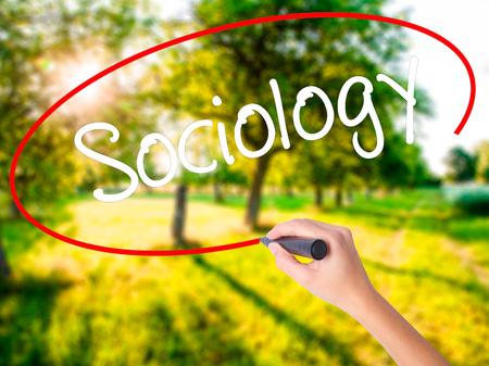 sociologia: Mujer escritura de la mano a bordo de Sociología transparente blanco con un marcador aislado sobre el fondo verde del campo. Foto de stock