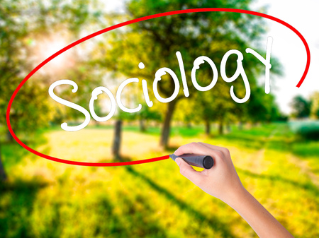 Woman Hand Writing Sociology  on blank transparent board with a marker isolated over green field background. Stock Photo Stock Photo