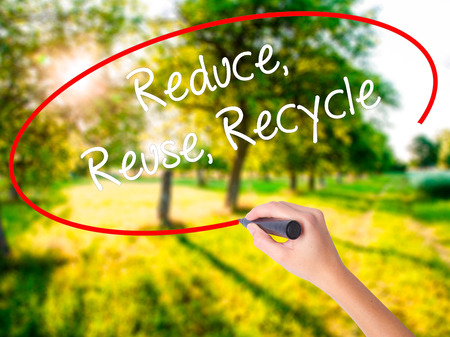 reduce reuse recycle: Woman Hand Writing Reduce Reuse Recycle on blank transparent board with a marker isolated over green field background. Stock Photo