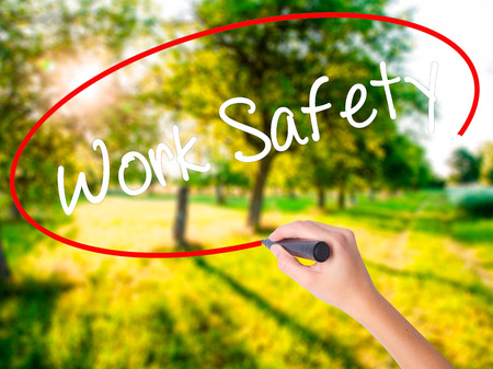 Woman Hand Writing Work Safety on blank transparent board with a marker isolated over green field background. Business concept. Stock Photo Stock Photo