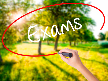 Woman Hand Writing Exams on blank transparent board with a marker isolated over green field background. Business concept. Stock Photo