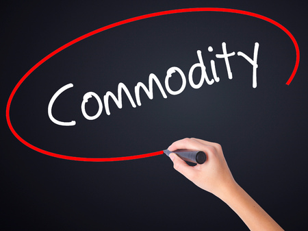 commodity: Woman Hand Writing Commodity on blank transparent board with a marker isolated over black background. Business concept. Stock Photo