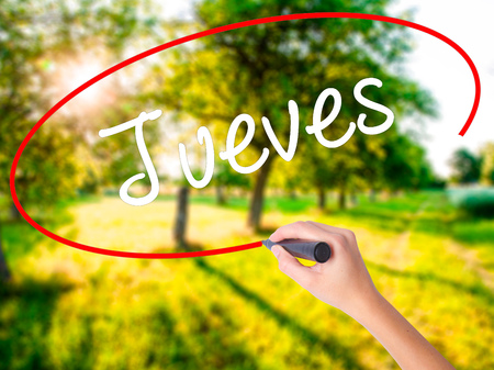 Woman Hand Writing Jueves (Thursday in Spanish) on blank transparent board with a marker isolated over green field background. Business concept. Stock Photo