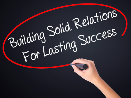 lasting: Woman Hand Writing Building Solid Relations For Lasting Success on blank transparent board with a marker isolated over black background. Business concept. Stock Photo