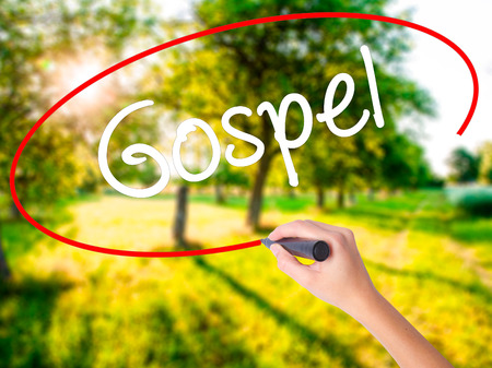 gospel: Woman Hand Writing Gospel  on blank transparent board with a marker isolated over green field background. Stock Photo