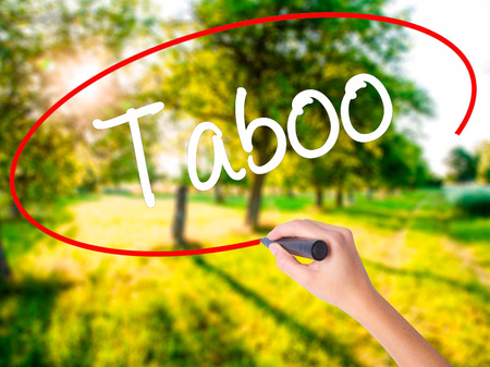 Woman Hand Writing Taboo on blank transparent board with a marker isolated over green field background. Stock Photo Stock Photo