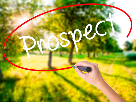 Woman Hand Writing Prospect on blank transparent board with a marker isolated over green field background. Business concept. Stock Photo