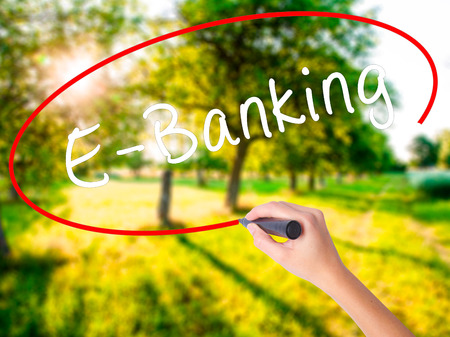 technology transaction: Woman Hand Writing E-Banking on blank transparent board with a marker isolated over green field background. Business concept. Stock Photo Stock Photo