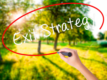 downsize: Woman Hand Writing Exit Strategy on blank transparent board with a marker isolated over green field background. Stock Photo