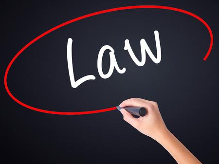 Ley de la escritura de la mano de la mujer en el tablero transparente en blanco con un marcador aislado sobre fondo negro. Concepto de negocio. Foto de stock Foto de archivo