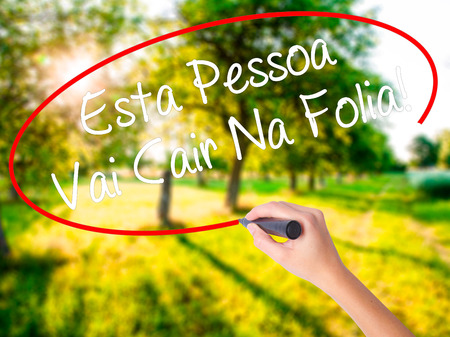 Woman Hand Writing Esta Pessoa Vai Cair Na Folia! (This Person Will be at Carnaval in Portuguese) on blank transparent board with a marker isolated over green field background. Stock Photo