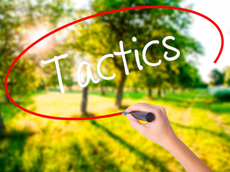 Woman Hand Writing Tactics on blank transparent board with a marker isolated over green field background. Stock Photo