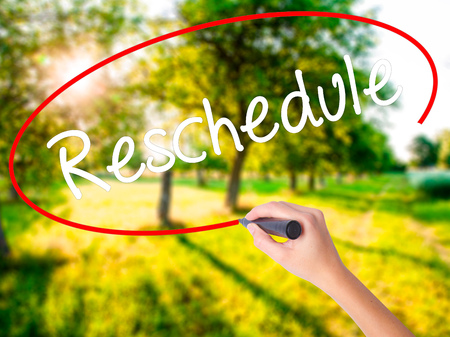 adjourned: Woman Hand Writing Reschedule  on blank transparent board with a marker isolated over green field background. Stock Photo