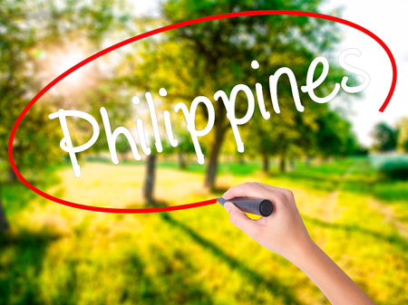 underdeveloped: Woman Hand Writing Philippines on blank transparent board with a marker isolated over green field background. Business concept. Stock Photo