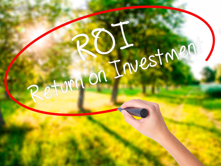 Woman Hand Writing ROI  Return on Investment on blank transparent board with a marker isolated over green field background. Business concept. Stock Photo Stock Photo