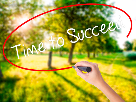 Woman Hand Writing Time to Succeed on blank transparent board with a marker isolated over green field background. Business concept. Stock Photo