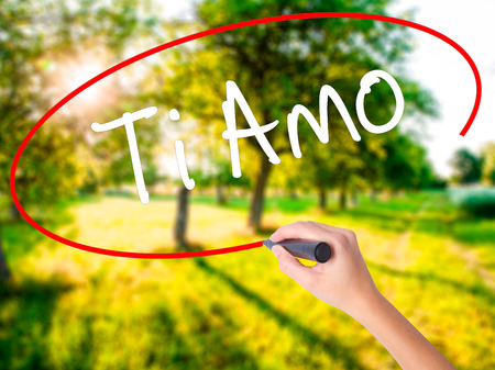 Woman Hand Writing Ti Amo (I Love You In Italian) with a marker over transparent board . Isolated on background. Business, technology, internet concept. Stock  Photo