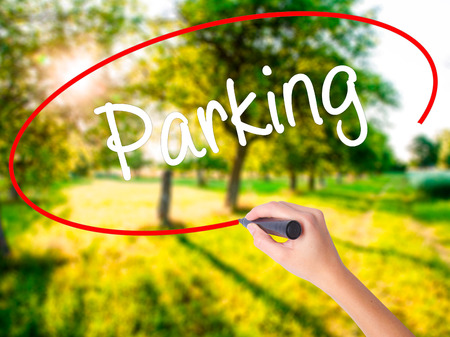 Woman Hand Writing Parking on blank transparent board with a marker isolated over green field background. Business concept. Stock Photo